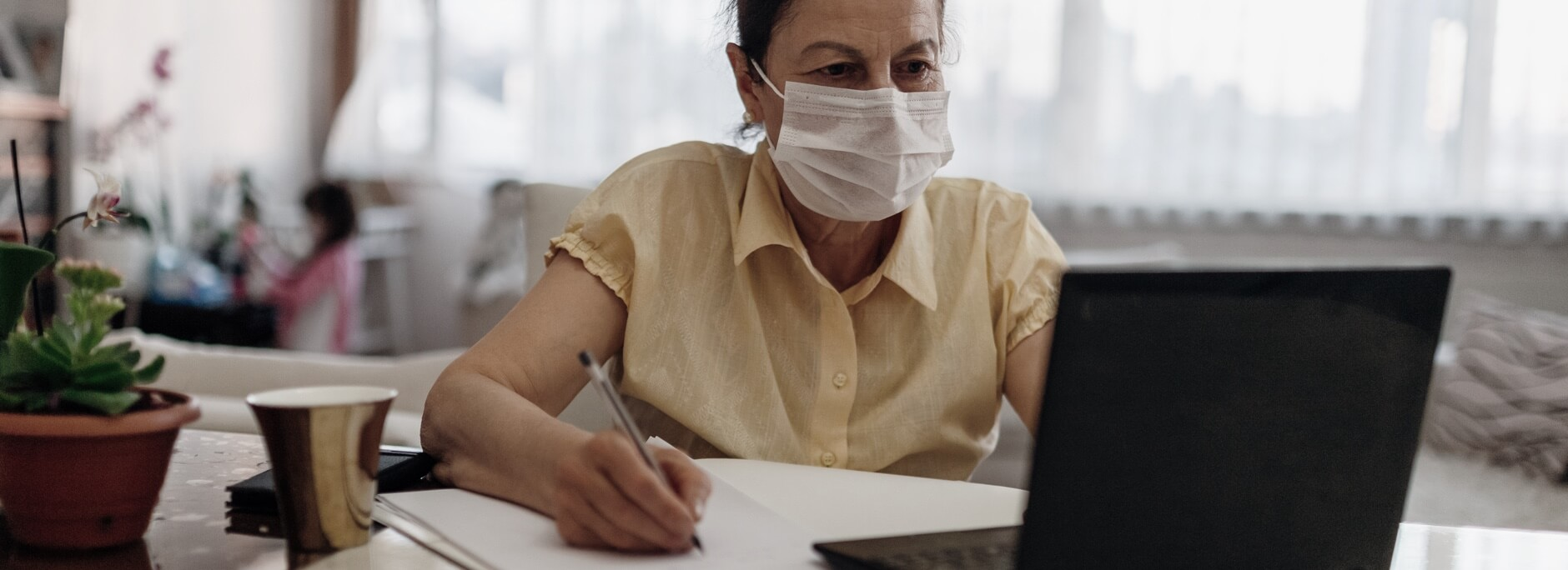 Woman with Mask Working on Computer