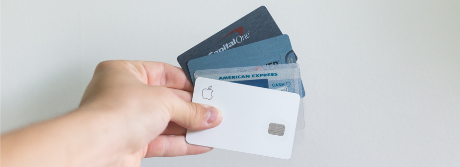 Hand holding multiple credit cards and debit cards for online shopping